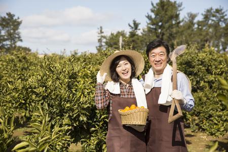 フィールドに立っている中年アジア農民カップル 写真素材