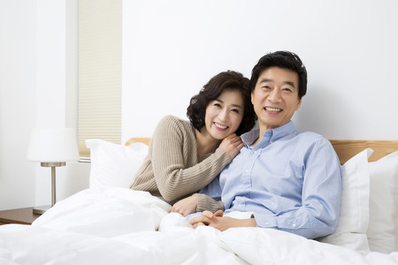 Middleaged Asian Couple Smiling in Bed Stock Photo