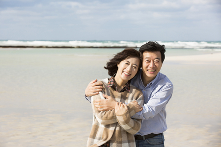 해변에 미소 짓는 중간 아시아 커플 스톡 콘텐츠