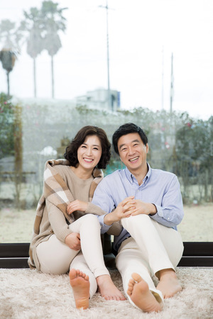 Middleaged Asian Couple Smiling and Sitting on Rug In Livingroom Stock Photo - 66109040