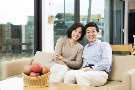 Middleaged Asian Couple Smiling in the Living room Stock Photo