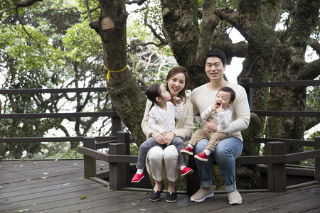 森の中のベンチに座って幸せなアジア家族 写真素材