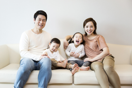 family sofa: Happy Asian Family Smiling on the Sofa at Home