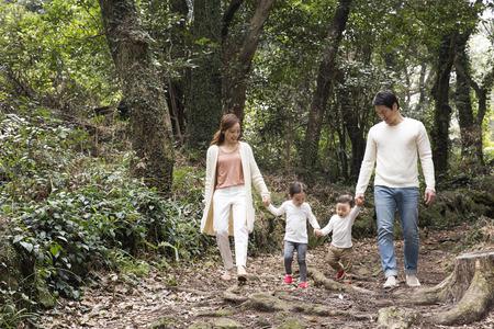 Famiglia asiatica felice che camminano insieme nella foresta