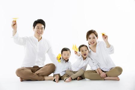 Feliz familia volando avión de papel amarillo - aislado en blanco Foto de archivo