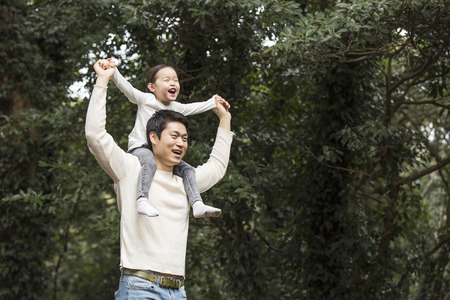 Happy Father Giving Daughter Piggyback Ride on His Shoulders in the Forest