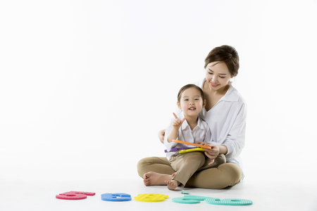 Little Asian Girl Sitting on Mothers Lap,Playing with Sponge DigitsNumbers - Isolated on White