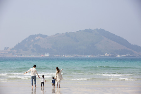 Happy Asian Family Holding Hands,Looking out at the Ocean