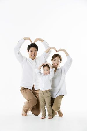 Feliz familia asiática posando, haciendo corazón firme con los brazos - aislados en blanco