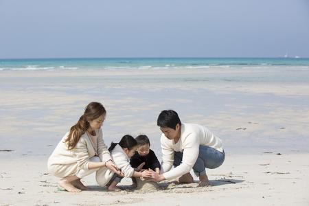 Happy Asian Family Building Sandcastle on the Beach