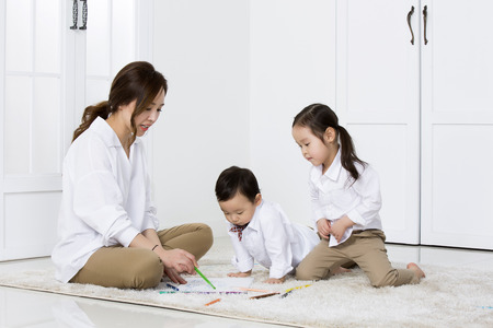 asian family: Asian Mother Showing How to Draw to Her Kids at Home