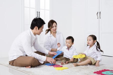Feliz familia asiática jugando con dígitos / números de esponja en el hogar Foto de archivo - 66105255