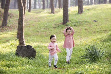Cute Asian Boy and Girl Rire et courir sur l'herbe dans la forêt