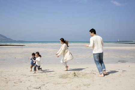 Genitori asiatici felici che giocano con i bambini sulla spiaggia