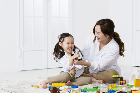 Asian Mother and Daughter Playing with Building Blocks at Home