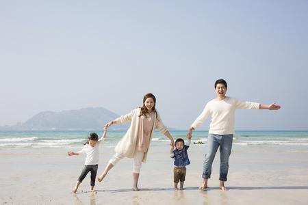 Gelukkige Aziatische Handen Family Holding en Walking on Beach