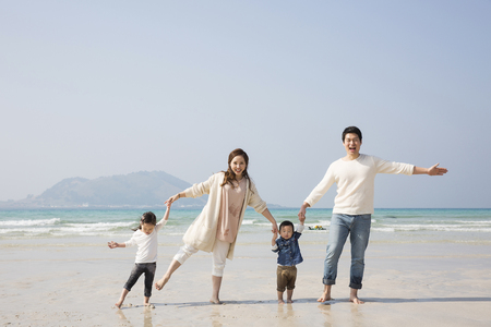 Happy Asian Family Holding Hands and Walking on Beach Imagens