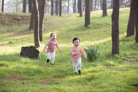 Lindo niño y niña asiática riendo y corriendo sobre la hierba en el bosque