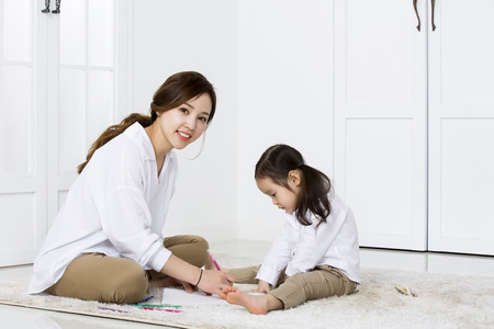 Asian Mother Showing How to Draw to Her Daughter at Home