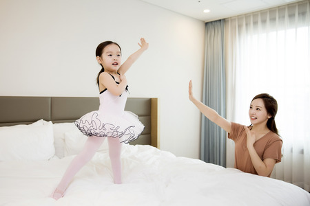 Asian Mother and Daughter Posing Ballet Moves in the Bedroom