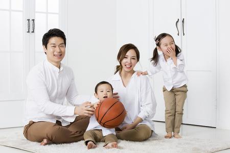 семья: Счастливая азиатская семья улыбается и позирует дома
