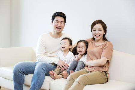 Gelukkig Aziatische Familie Het glimlachen op de bank thuis Stockfoto