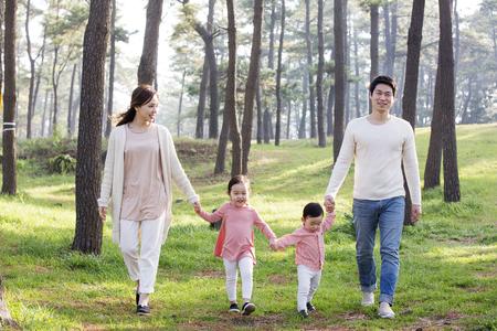 幸せのアジア家族の手を繋いでいると森を歩く