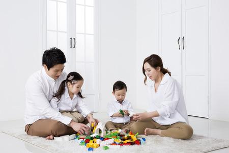 Familia asiática feliz que juega con los bloques huecos en el país Foto de archivo