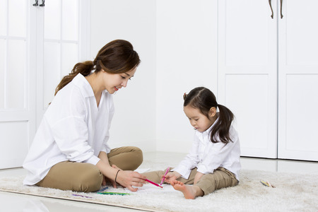asian family: Asian Mother Showing How to Draw to Her Daughter at Home