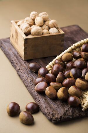unsaturated: Walnuts and Chestnuts on a Wooden Board Stock Photo
