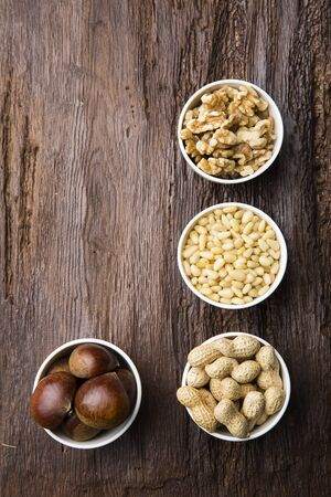 unsaturated: Different Types of Nuts in White Bowls from High Angle View with Wooden Background
