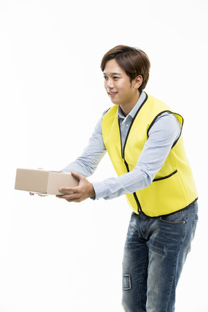 Young Asian Man in a Yellow Vest Giving a Cardboard Box