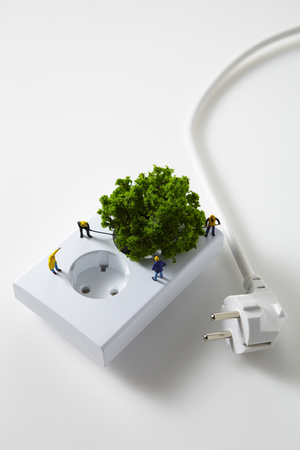 Mini tree plugged into white outlet isolated Stock Photo
