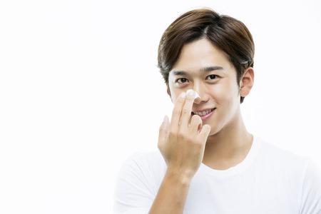 Young Asian Man Applying Moisturizer