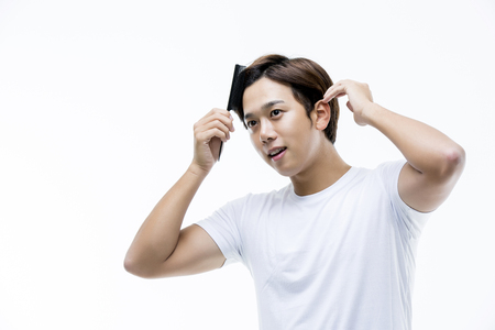 stylish hair: Young Asian Man Brushing His Hair Stock Photo