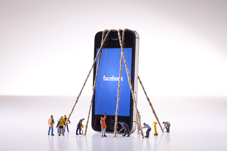Smartphone with facebook being held down