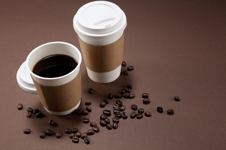 Due bicchieri di carta di caffè e qualche chicco di caffè