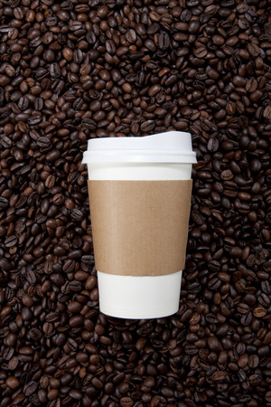 Una tazza di caffè in carta con sfondo di chicco di caffè Archivio Fotografico
