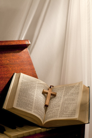 Open bible with a wooden cross in the middle