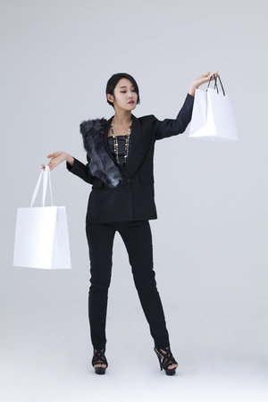 fancy bag: A woman dressed in black shopping