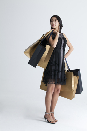 A woman in dark dress holding shopping bags