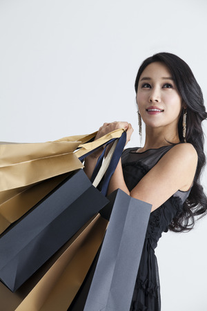 fancy bag: A woman in dark dress holding shopping bags