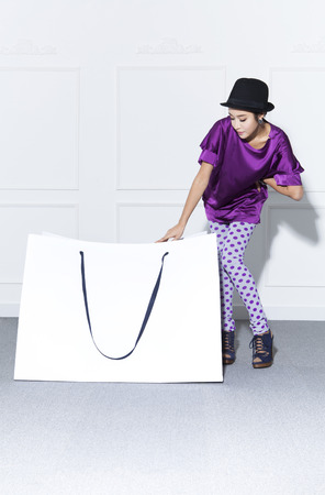 A woman in black derby hat with a giant white shopping bag