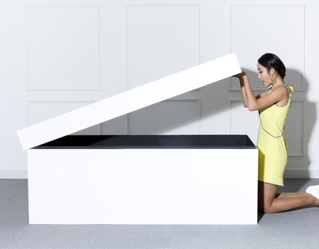 shoe box: A woman in yellow dress with a giant shoe box