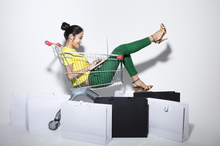 cart: A woman in yellow and green with a shopping cart and bags