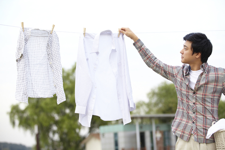 Father Taking Down Clothes Outdoors Stock Photo