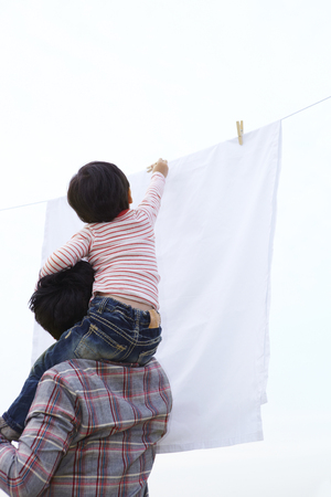 Father And Son Hanging Clothes Outdoors