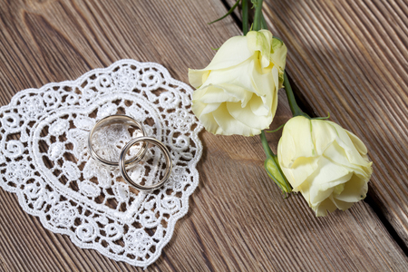 Wedding Rings Placed Next To Roses