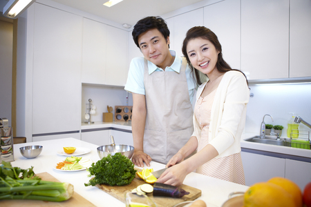 standing together: Father And Mother Cooking In The Kitchen