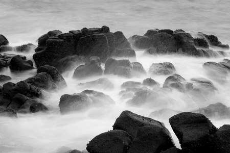 physical geography: Waves hitting rocks in the ocean Stock Photo
